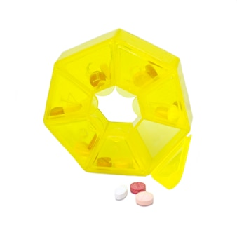Pink tablets in a yellow pillbox for drugs