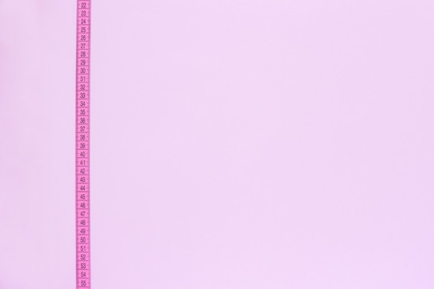 Pink tape measure vertically crosses pink background.