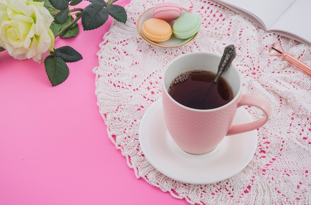 Pink tea cup with macaroons on lace tablecloth against pink background