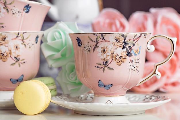 꽃 장식과 마카롱 과자 핑크 티 컵