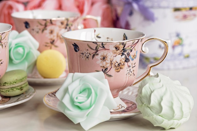Pink tea cups with floral ornament and macaroon sweets