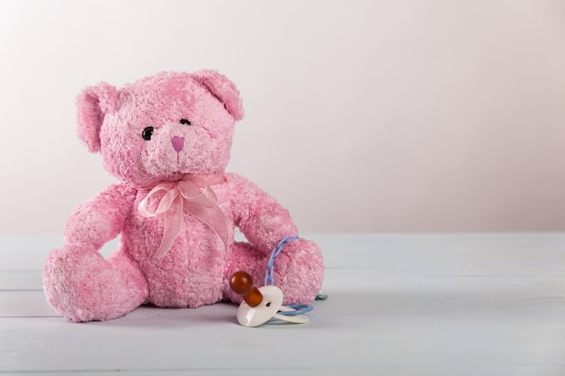 Pink teddy bear and dummy