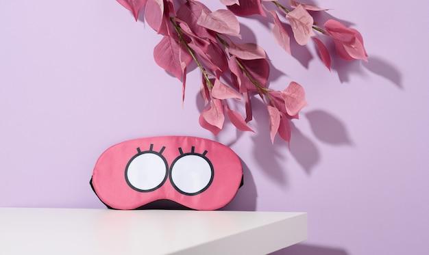白いテーブルの上のピンクのテキスタイル睡眠マスク