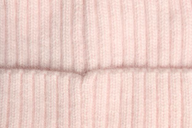 ピンクの質感のウールのクローズアップ、織布、ニット生地
