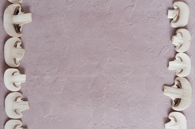 ピンクの織り目加工の表面とキノコのスライスのフレーム