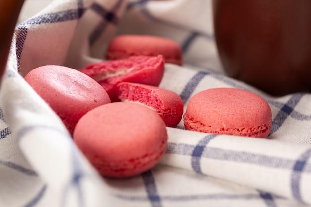 テーブルクロスにピンクの小さなマカロンクッキーをクローズアップ