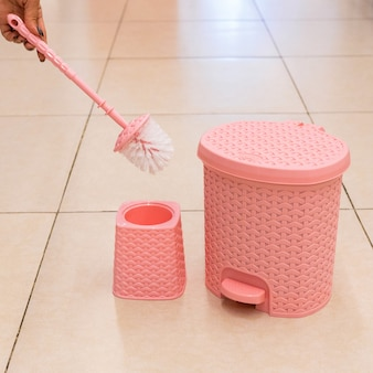 Pink toilet brush and holder, trash bin isolated
