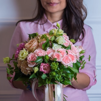 Pink tonned rose flower bouquet in the hands of a woman