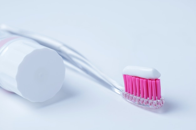 Pink toothbrush and toothpaste on white background