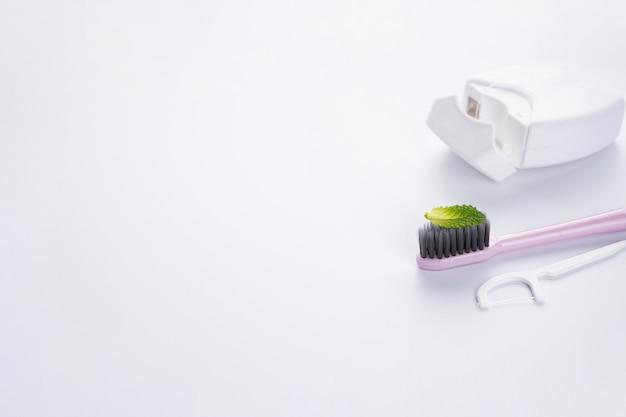 Розовая зубная щетка с белой зубочисткой и зубной нитью на белом