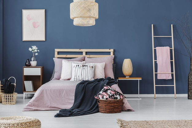 Pink towel on ladder next to bedside cabinet with design lamp in bedroom with king-size bed