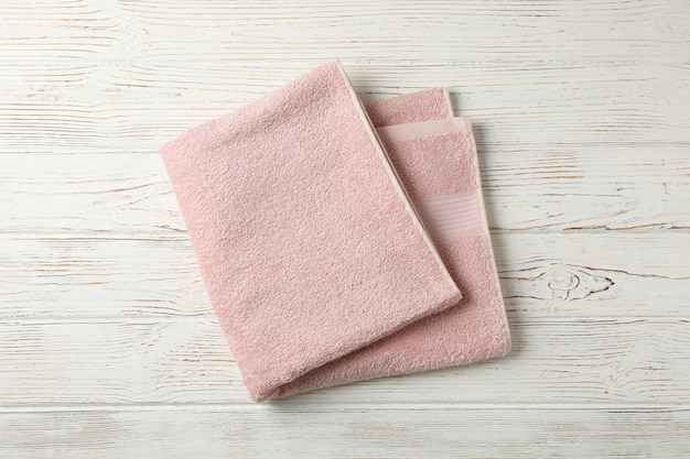 Pink towel on white wooden background, top view