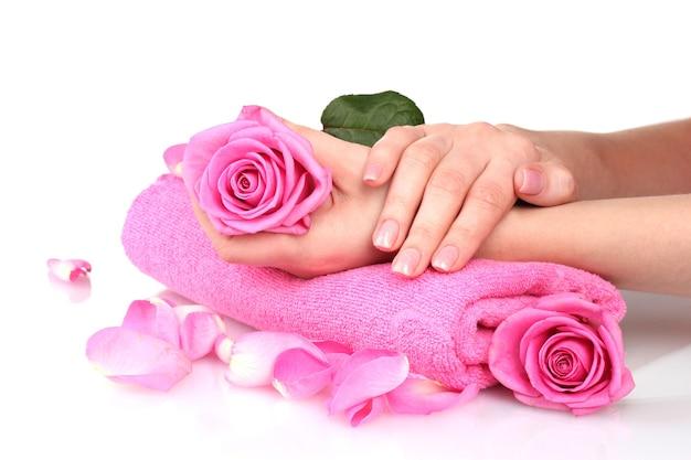 Розовое полотенце с розами и руками на белом столе