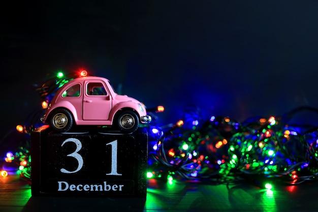 新年のライトを背景にピンクのおもちゃの車