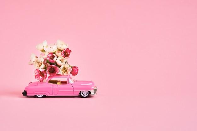 핑크 backgroun에 꽃 꽃다발을 제공하는 핑크 장난감 자동차. 꽃 배달 개념. 공간 복사