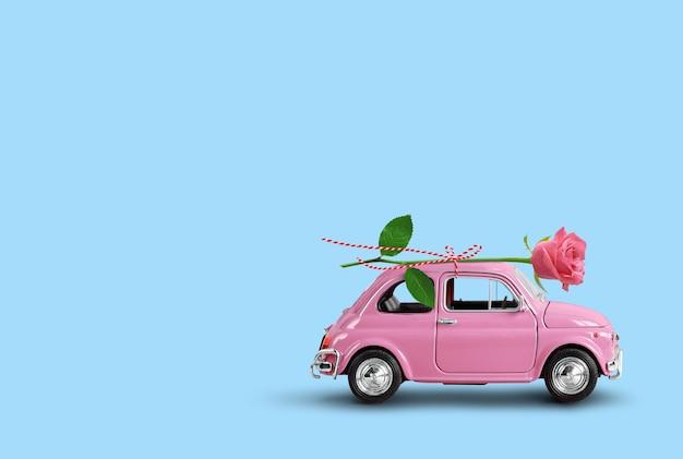 파란색 배경에 분홍색 장미 꽃을 배달하는 분홍색 장난감 자동차. 발렌타인 데이, 꽃 배달, 여성의 날. 텍스트에 대 한 장소입니다.