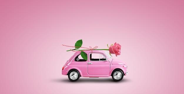 분홍색 배경에 분홍색 장미 꽃을 배달하는 분홍색 장난감 자동차. 발렌타인 데이, 꽃 배달, 여성의 날. 텍스트에 대 한 장소입니다.
