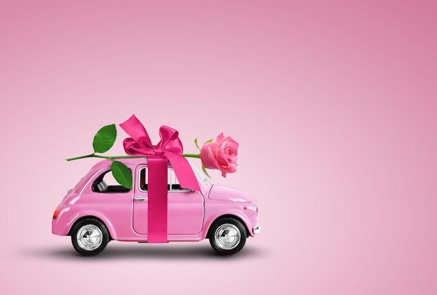 분홍색 장난감 자동차는 리본과 보원 분홍색 배경이 있는 분홍색 장미 꽃을 배달합니다. 발렌타인 데이, 꽃 배달, 여성의 날. 텍스트에 대 한 장소입니다.