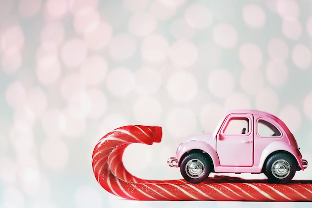 Pink toy car skiing on candy canes. greeting card new year, christmas