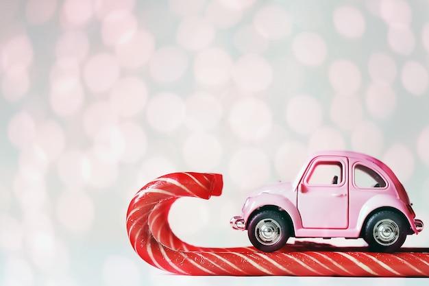 キャンディケインでスキーをするピンクのおもちゃの車。グリーティングカードお正月、クリスマス