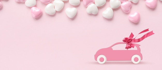 Pink toy car with gift bow on a pink background with valentines hearts