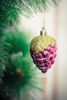 ピンクのおもちゃ:ガラス松ぼっくりが緑の枝のクリスマスツリーに掛かっています。