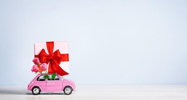 Розовый игрушечный ретро-автомобиль с подарочной коробкой на крыше с букетом роз на синем фоне. скопируйте пространство.