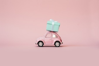 Pink toy retro model car delivering gift box on pink background
