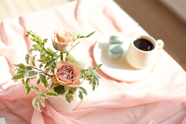 Pink transparent tablecloth on a wooden white table a cup of coffee or tea with french macaroons.