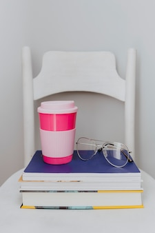 Pink travel mug on a stack of textbooks