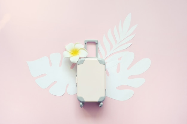 Pink travel suitcase on pink background with tropical leaves and white flower