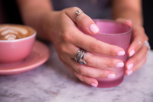 美しい女性の手で保持されているカプチーノのピンクのトレンディなカップ Premium写真