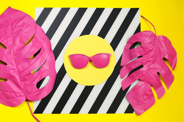 Pink tropical palm leaf of monstera and sunglasses