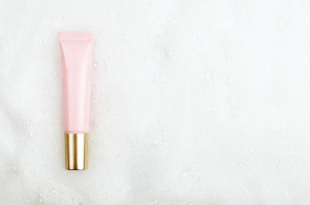 泡と白い泡の背景に金色のキャップとジェルまたはフェイスクリームのピンクのチューブ。コピースペース、平面図、フラットレイアウト。