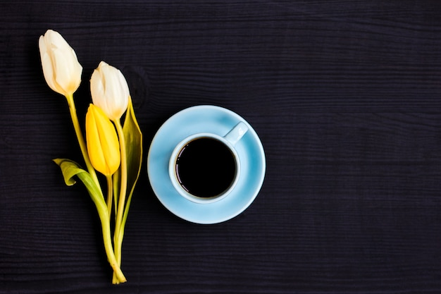 Pink tulip and blue coffee cup on black wooden surface
