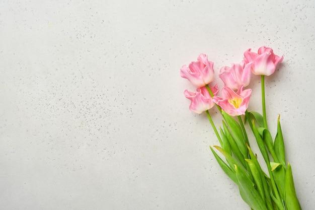 灰色の背景の前にハッピー イースターのピンクのチューリップの花の花束