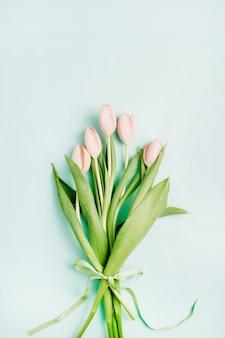 青の背景にピンクのチューリップの花の花束。フラットレイ、トップビュー