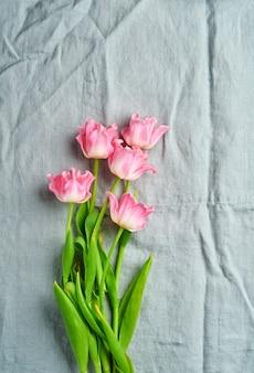 회색 리넨 냅킨 배경 앞에 분홍색 튤립 꽃 꽃다발