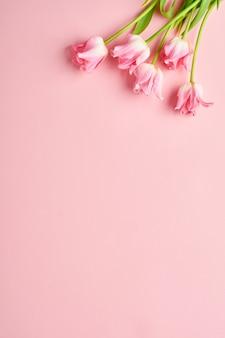 ピンクの背景の前にピンクのチューリップの花の花束