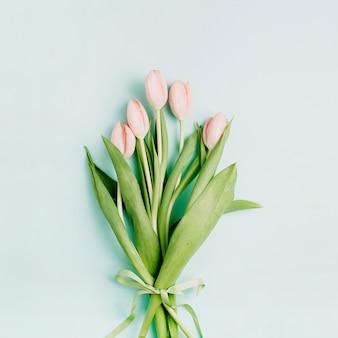 옅은 파란색 배경에 핑크 튤립 꽃 꽃다발입니다. 평면 위치, 평면도