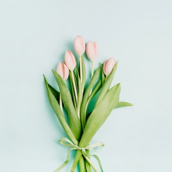 Pink tulip flowers bouquet on pale blue background. flat lay, top view