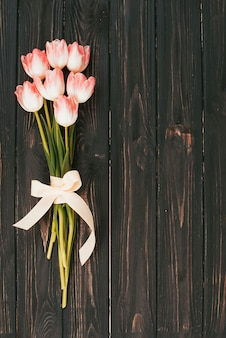 Pink tulip flowers bouquet on wooden table