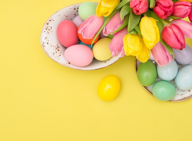 Pink tulip flowers easter eggs decoration yellow background