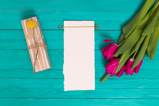 Pink tulip flowers; gift box; and blank white paper on green background