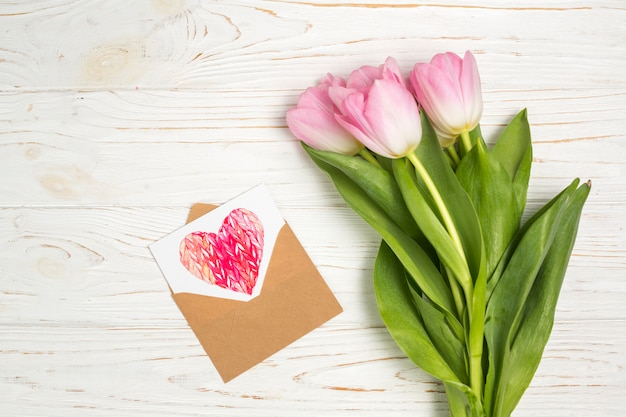 Pink tulip flowers with heart drawing in envelope