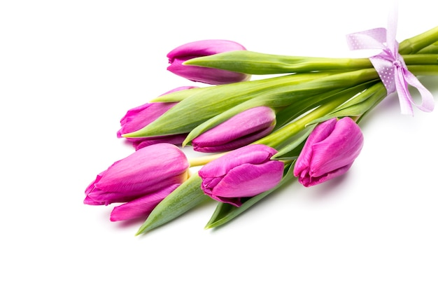 Pink tulip flowers with violet ribbon on the grey surface