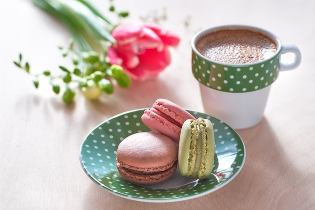 Pink tulip, freesia, espresso and macarons in front, spring flowers in the back