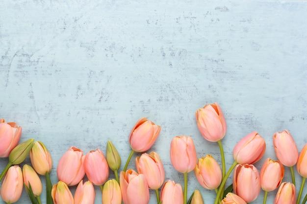 ヴィンテージの木製の背景にピンクのチューリップ。母の日グリーティングカード。