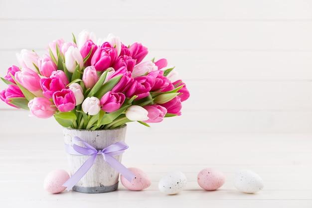 白い背景の上のピンクのチューリップ。イースターと春のグリーティングカード。