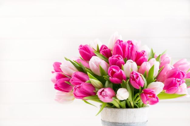Розовый тюльпан на белой открытке пасхи и весны.